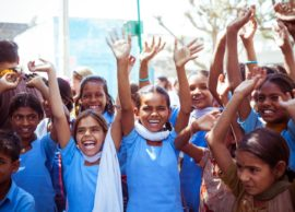 Sabbalpura, India - March 15, 2014: Group of indian school children - girls and boys wearing school uniforms posing in the rural village with raised hands, Rajasthan, India.